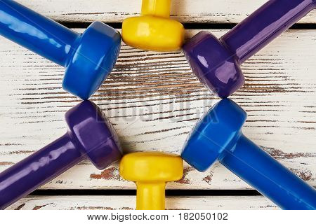 Coloured dumbbells on wooden backdrop. Key to healthy life.