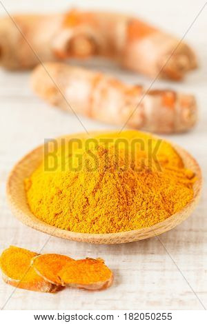 Turmeric root and turmeric powder on a table