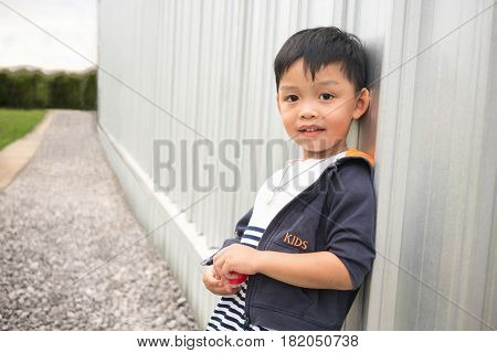 Happy cute boy leaning wall of building and perspective way background