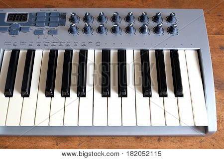 Electronic synthesizer keyboard with many control knobs in plastic body on wooden background front view closeup
