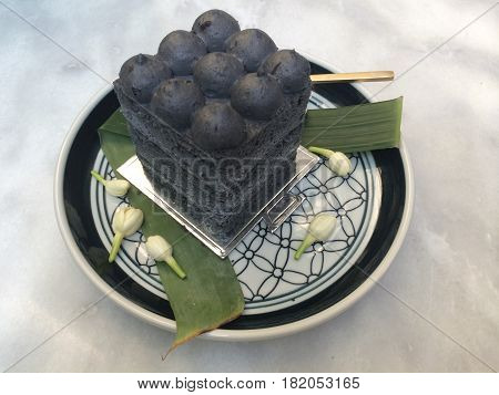 Start your day with homemade Gourmet pastry coconut and charcoal cake in the cafe with blur background black and white cake fusion stylish dessert tea time Thai dessert