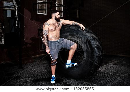 Strong and fit bearded man standing near the tire. Crossfit training