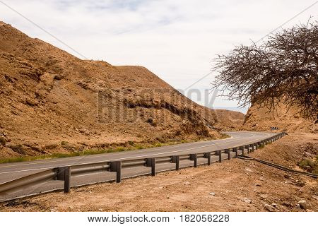 Highway in a yellow stone desert to dead sea in Israel.