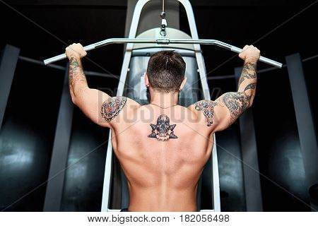 Athlete with tattooed naked torso doing exercise on the back muscles in a block simulator. Back view of bodybuilder exercising on simulator. Training for back muscles