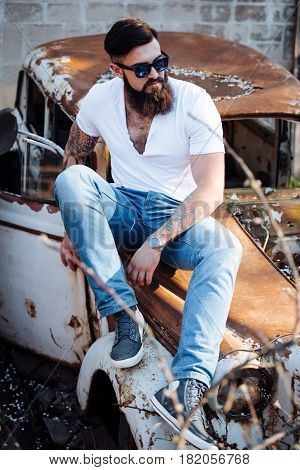 Brutal bearded man with tattoo in jeans clothes is sitting on the hood of the old car