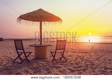 Wooden table and chairs with umbrella on the beach at sunset.