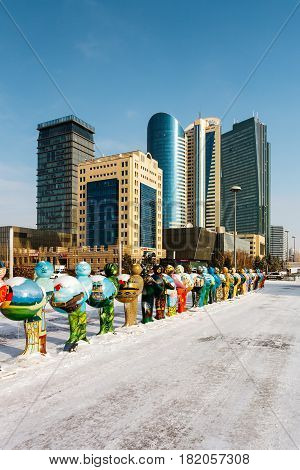 Expo-men, symbolizing the countries-participants of EXPO-2017, against the backdrop of the business center of Astana, Kazakhstan.