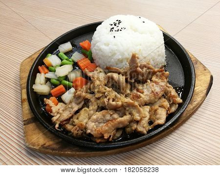 Grill pork slice on the hot BBQ pan with vegetable serve with rice stir fried pork with garlice lunch set meal ready to eat quick meal Thai food focus-on-foreground with blur background top view