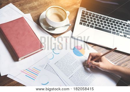Closeup business woman hand writing on graph financial diagram document with pencil. Laptop a cup of coffee and notebook on wooden table.