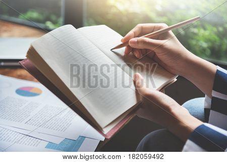 Closeup woman hands writing on a notebook.