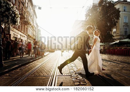 Elegant Bride And Groom Running And Smiling In European City Street At Evening. Luxury Emotional Wed