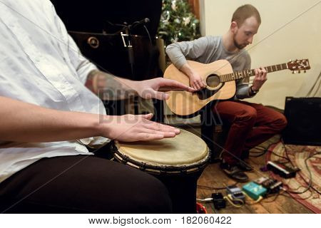 stylish solo guitarist and percussionist playing on a concert on a background of his band