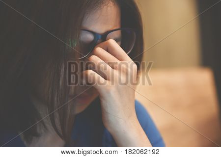 Tired Asian eyeglasses woman rubbing eyes. Copy space. Overtime. Overwork.