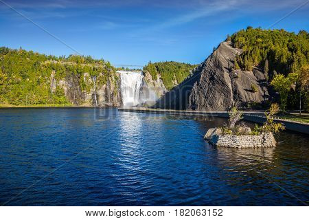 Small picturesque artificial island on the lake. Above the waterfall built bridge for walking. Montmorency Falls Park, in Quebec. The concept of active and cultural tourism