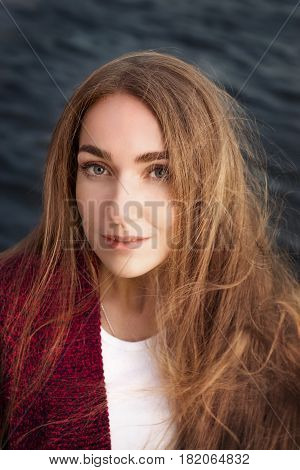 Young woman with long wild hair against dark water. Warm toned beauty portrait