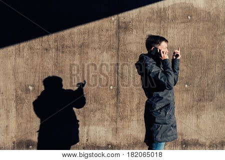 Serious authentic woman with short hair talking on mobile phone on the street in the under passage winter setting sun casting contrasty shadows on the wall