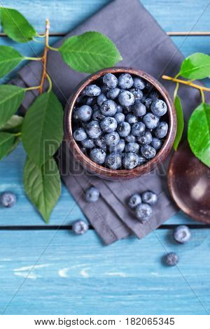 Freshly blueberries in metal bowl. Juicy and fresh blueberries with green leaves on blue wooden table. Blueberry on wooden background. Blueberry antioxidant. Concept for healthy eating and nutrition.