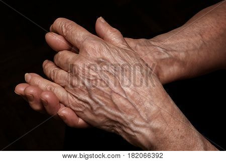 Folded senior woman wrinkled hands close up. On abstract background clipping path included. Old age age problems poverty and loneliness theme
