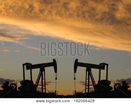 Two black pumper jacks with orange clouds