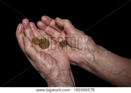 Senior woman hands holding some euro coins. Pension poverty social problems and senility theme. Isolated on black clipping path included
