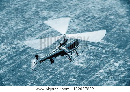 Black helicopter flying in front. Light multipurpose helicopter five-seat all-metal construction. With one three-bladed main rotor and one two-blade tail rotor. The machine is equipped with fixed landing gear.