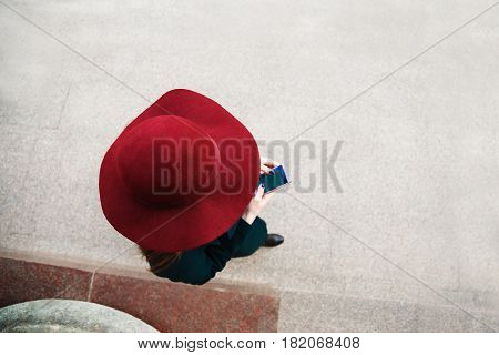 Woman in hat strolls around the city and uses her mobile phone. View from above.