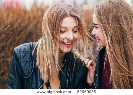 Two lovely young women talking and telling secrets