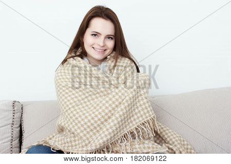 girl is sitting on the sofa under the rug