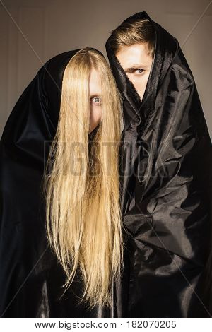 The anonymous girl with long blonde hair and a man in black cloth. Conceptual anonymous photography. Piercing look. Anonymity.