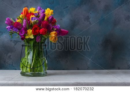 bunch of bright spring flowers in vase on dark background with copy space