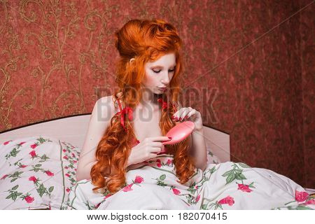 Woman with long red curly hair gathered into braids and comb in hand in nightgown in bed under blanket. Red-haired girl with a pretty face pale skin bright appearance in a bedroom combing her hair