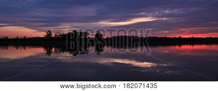 Dramatic sky at sunset mirroring in lake Pfaffikon Switzerland.