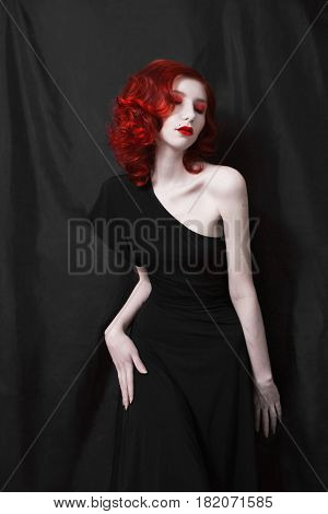 Stylish woman with red curly hair in a black skin-tight stylish dress on a black background. Red-haired stylish girl with pale skin a thin waist blue eyes a bright unusual appearance red lips. Retro makeup. Stylish model