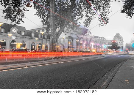 Toulouse, France - October 27, 2016; Light trails from passing vehicles against monochrome background an evening city image with glow of lights on street and Matabiau Railway Station long exposure Toulouse France.