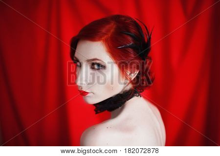 Noir woman with red curly hair in a black dress and retro makeup on a red background. Red-haired noir girl with pale skin blue eyes a bright unusual appearance red lips and a fatal face. Noir woman