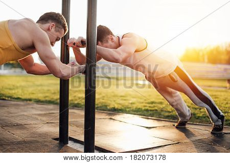 Two Man Stand At Stadium With Sunset Background