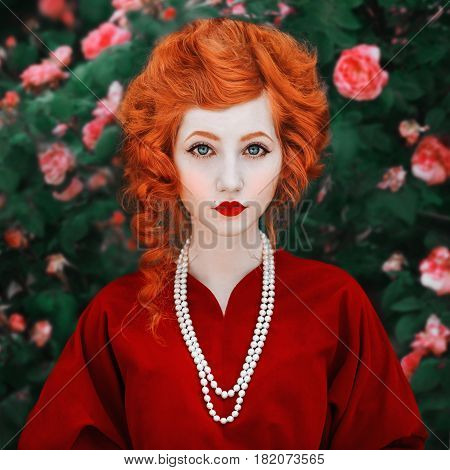 A woman with red hair and a red slinky dress posing on a background of red roses. Red-haired girl with pale skin and blue eyes with a bright unusual appearance with a necklace of beads around her neck. White beads. Necklace of beads. Beads on the head. Be