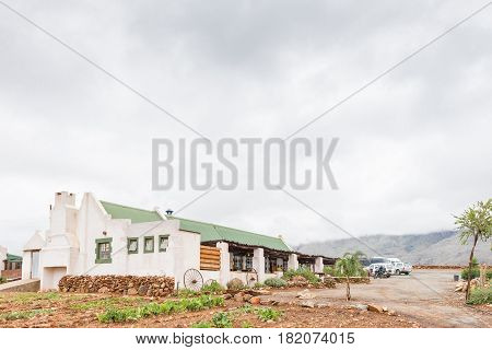 SWARTBERG SOUTH AFRICA - MARCH 24 2017: A well known landmark Kobus se Gat a restaurant at the start of the Swartberg Pass (black mountain pass). A vehicle is visible on the pass in the back