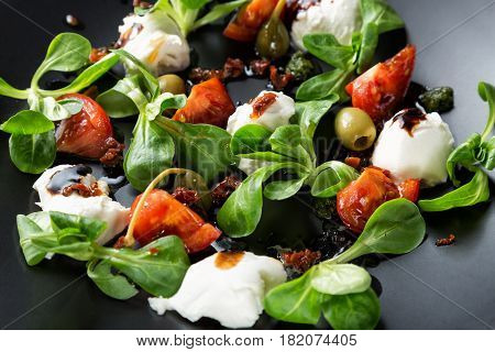 Caprese salad with mozzarella tomato basil and balsamic vinegar arranged on black plate. Close up image with selective focus.