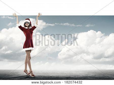 Full length of Christmas Santa girl holding white blank banner above head