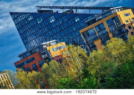 Seemingly pointed architecture shows blue cloudy sky in the foreground colored trees