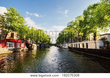 Spring sunny Amsterdam. The bright clear blue spring sky with white clouds. Boat trip on the canals of  spring Amsterdam. The bridge over the water. Travel to Europe in spring