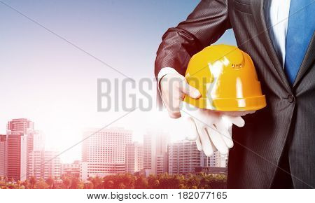 Close up of man in suit with construction helmet and gloves in hand