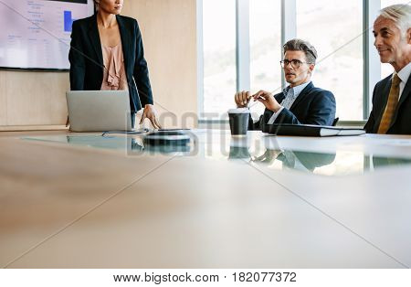 Businesspeople sitting at board room and discussing new strategies. Businessman and businesswoman meeting in conference room