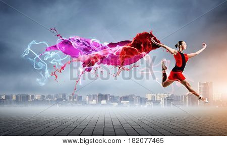 Gorgeous young ballet dancer wearing red dress over modern city background