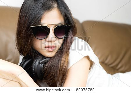 Sexy Asian girl wearing cool sunglasses and listen to dance music