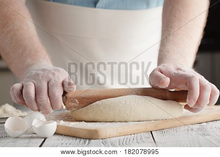 man rolling dough with a rolling pin