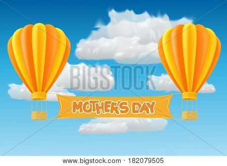 Yellow and orange air ballon with mother day banner fly past clouds