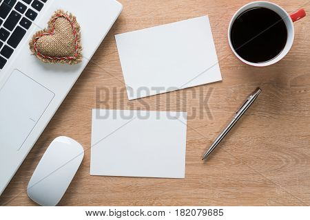 Laptop with coffee cup and notepad on wooden table