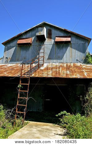 Rusty metal ladders lead to the second level on an abandoned and crumbling metal warehouse.